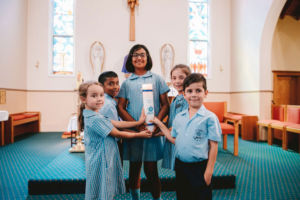 St Mary Star of the Sea Catholic Primary School Hurstville students holding school candle inside church