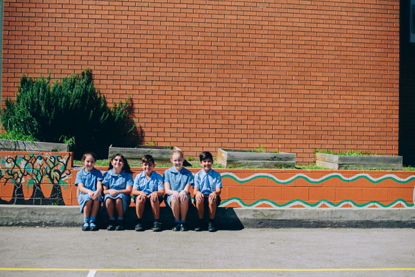 Students sitting and smiling in front of mural at St Mary Star of the Sea Catholic Primary School Hurstville