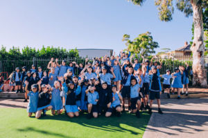 Large group of students smiling and waving at St Mary Star of the Sea Catholic Primary School Hurstville