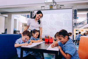 Teacher smiling at four students working at a table at St Mary Star of the Sea Catholic Primary School Hurstville