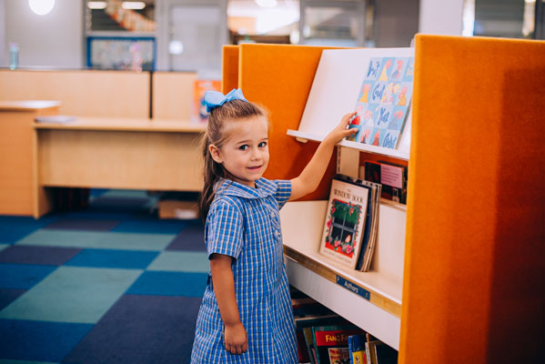 Girl looking at books in St Mary Star of the Sea Catholic Primary School Hurstville library