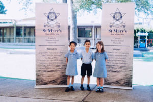 Three students standing in front of St Mary Star of the Sea Catholic Primary School Hurstville banners